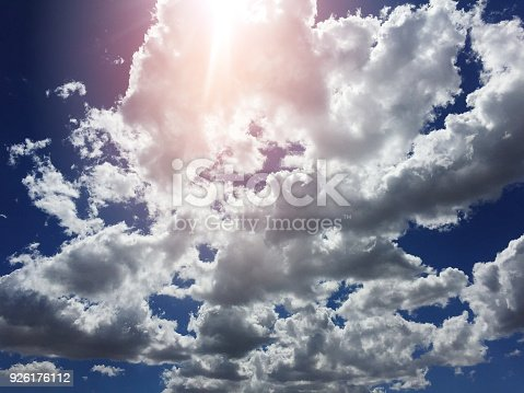 Dramatic afternoon cloudscape against a blue sky backdrop with orange sun lens flare Stellenbosch Cape Town South Africa