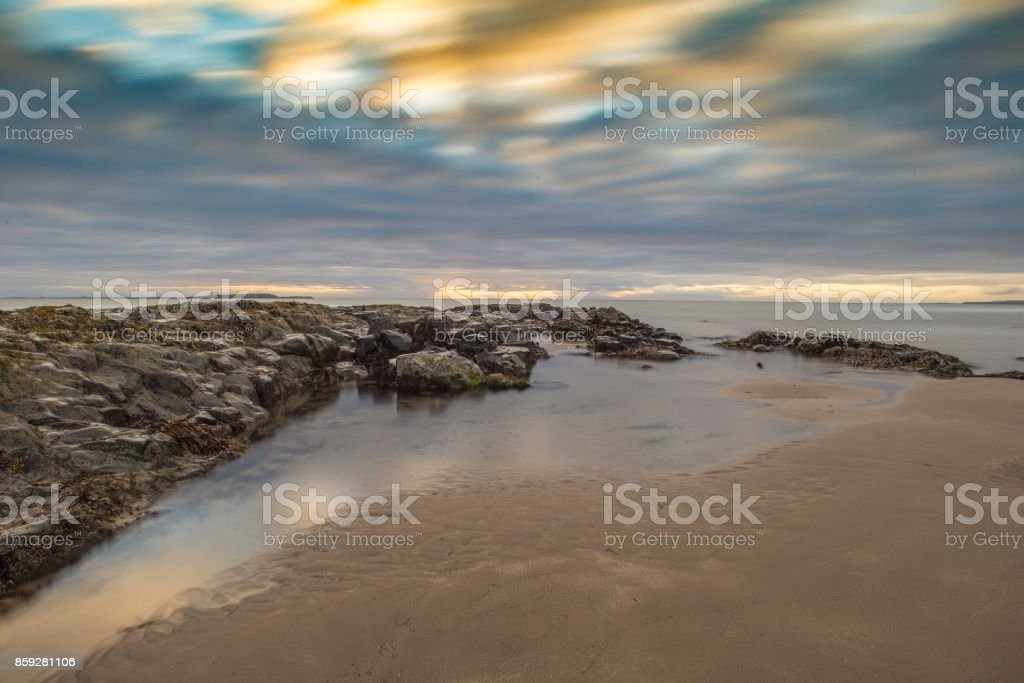 Cloud blur at sunrise over Bamburgh Beach, Northumberland stock photo