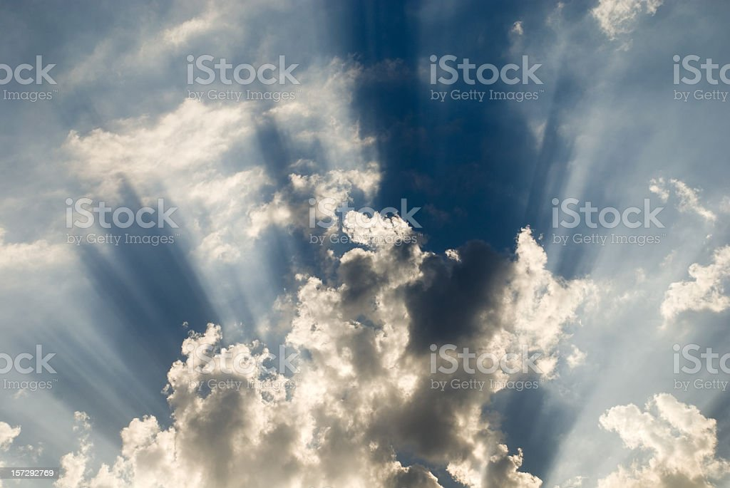 cloud in blue sky closes sun and casts aside rays royalty-free stock photo
