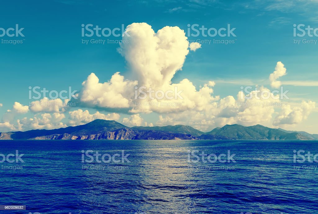 cloud in shape of heart over the island in sea, Sunny summer weather, Greece, Aegean stock photo