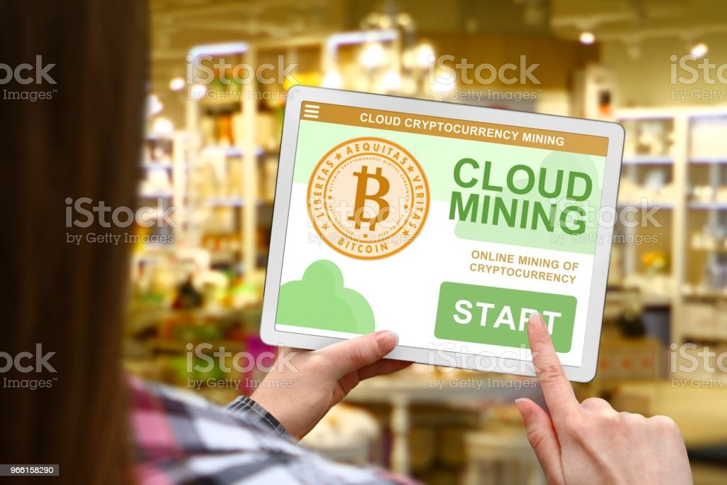 Cloud mining concept, girl holds the digital tablet on blurred shop background - Royalty-free Bitcoin Stock Photo