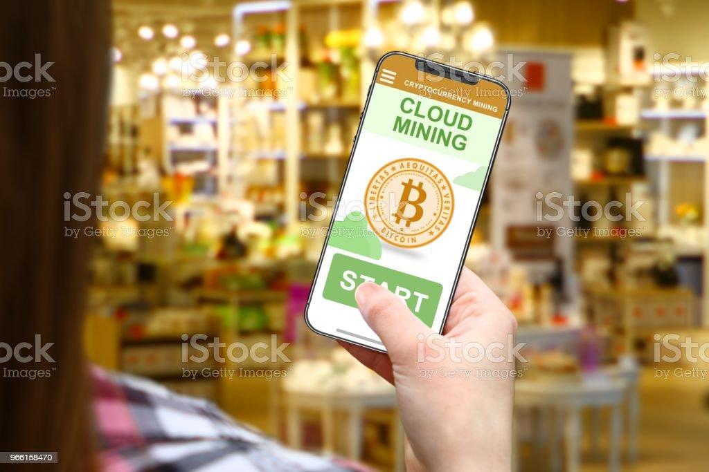 Molnet gruvdrift idé, flicka med Ramlösa telefon på suddig shop bakgrund - Royaltyfri Blockkedja Bildbanksbilder
