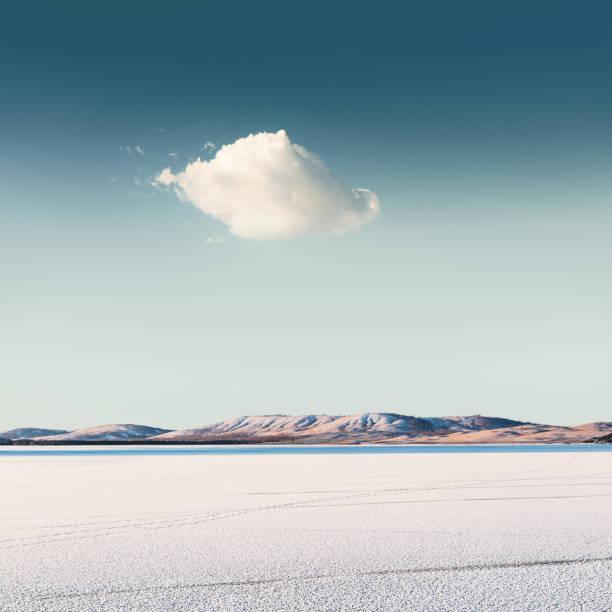 nuages sur un lac gelé - paysage zen photos et images de collection
