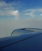 Cloud scape in blue sky with aeroengine and aircraft wing taken by phone through window on airplane