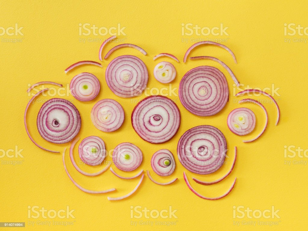 Cloud shape with sliced onion on yellow background stock photo