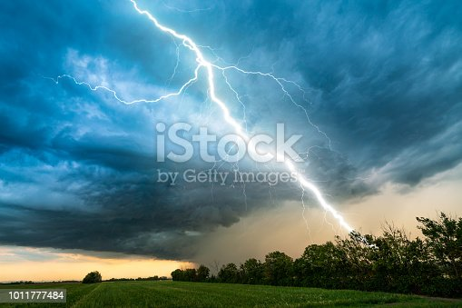 dramatic lightning thundertbolt bolt strike in daylight rural surrounding bad weather dark sky