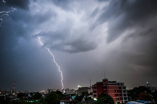 cloud to ground lightning strike in the city - lightning stock photos and pictures