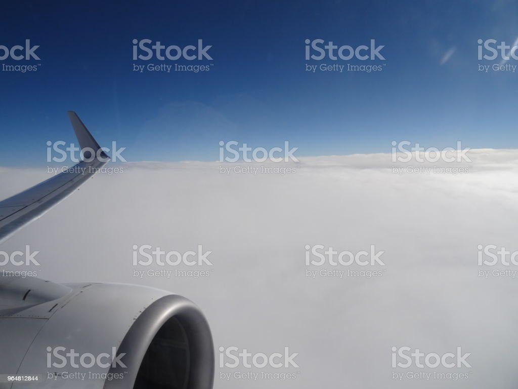 Cloud top view from with a jet engine in the foreground royalty-free stock photo