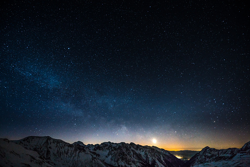 milky way night sky shot from obertauern austria snow covered mountain summits and rising moon