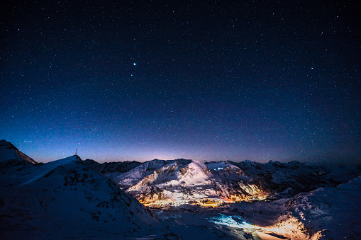 ski resort obertauern at night showing the light pollution of an alpine skiing town with nightsky stars