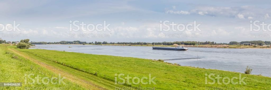 Vertroebeld rivierlandschap met een vervoer schip aan een rivier in Nederland foto