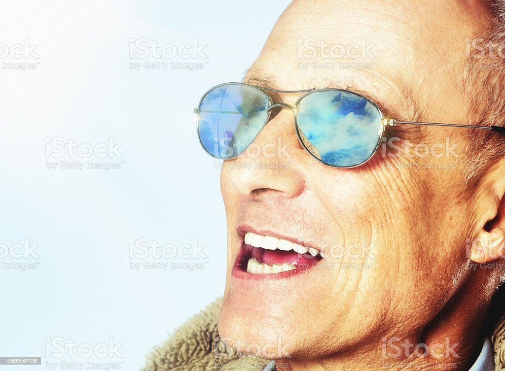 Clouded sky is reflected in smiling mature man's sunglasses stock photo
