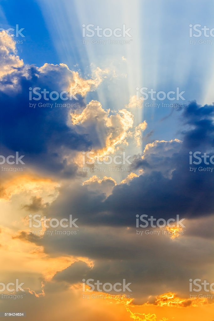 Clouds and a blue sky with a sunbeam shining through. stock photo