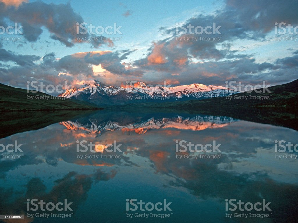 Clouds and mountains reflecting in the lake stock photo