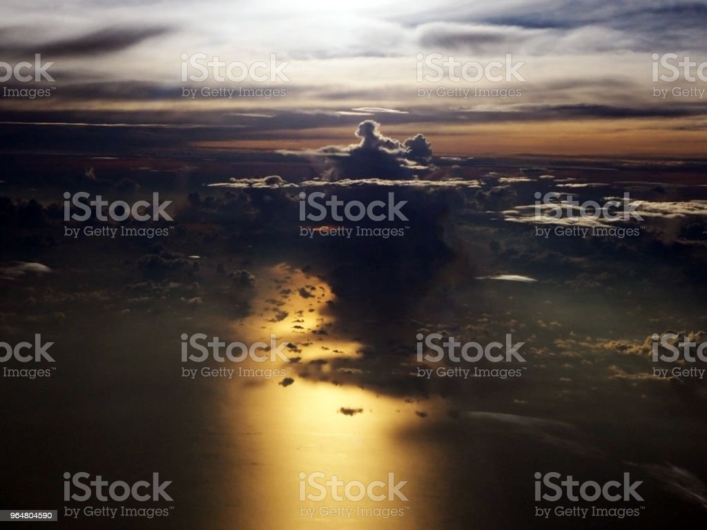 Clouds and purple sky as see through window of an aircraft,Before sunrise,Spectacular view of the sunshine above the clouds from airplan. royalty-free stock photo