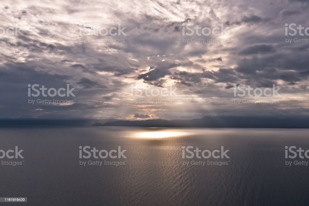 Clouds and rays of sun above the sea. Bright light with sun rays and...