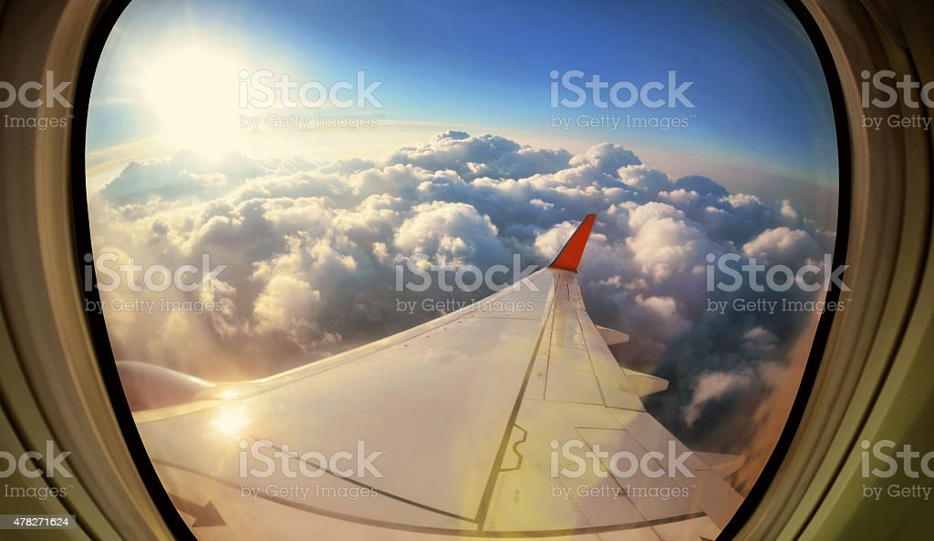 Clouds and sky as seen through window of  aircraft stock photo