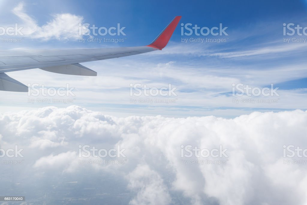 Clouds and sky as seen through window of an aircraft. Looking through window aircraft during flight in wing with a nice blue/purple/orange sky. ロイヤリティフリーストックフォト