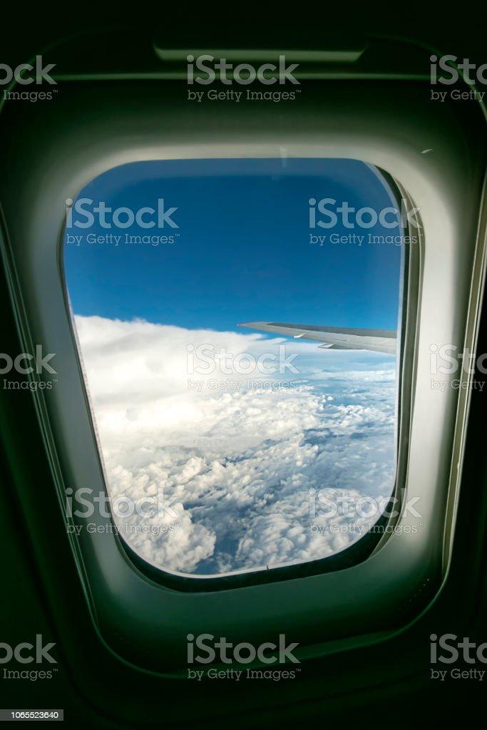 Wolken und Himmel gesehen durch Fenster eines Flugzeugs – Foto