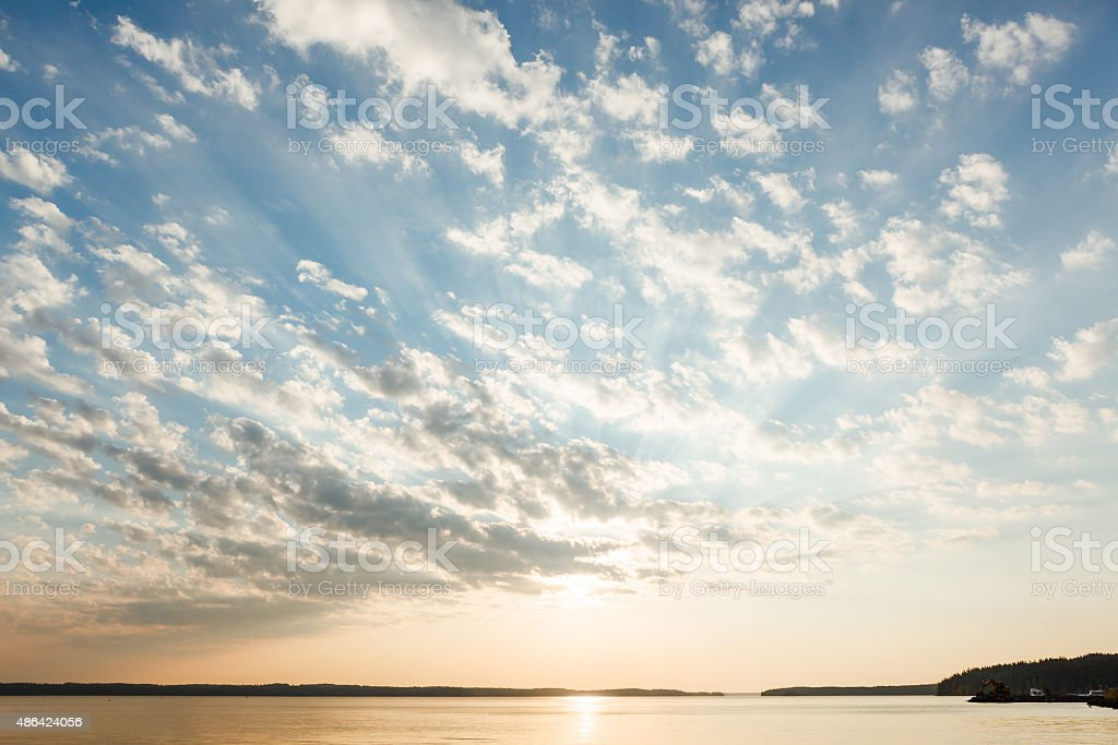 Clouds and sun rays over lake at sunrise stock photo