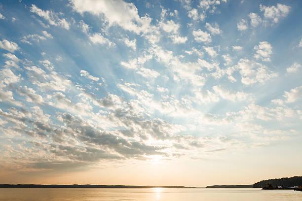 Nuvole e raggi di sole sopra il lago all'alba - foto stock