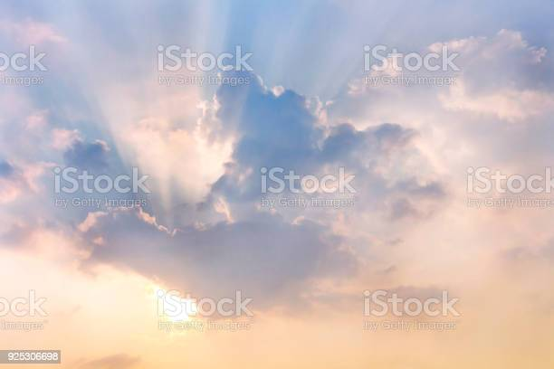 Photo of Clouds and sun shines through rays of light in the illuminated picturesque sky.