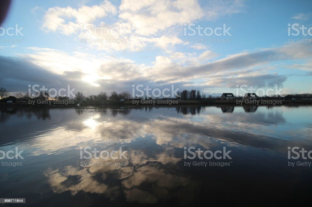 wolken en zonsopgang spiegels aan de Hollandse IJssel in Nederland foto