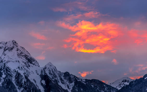 Clouds appear painted with bright red and orange in beautiful winter sunset stock photo