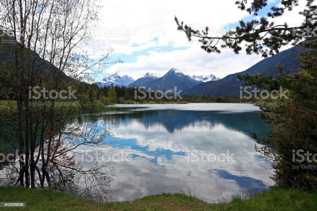 Clouds are reflected in a blue-turquoise lake at Weissenbach am Lech in Austria stock photo