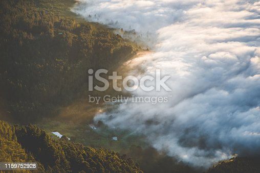 View above clouds, forests being covered by thick clouds. Beautiful, warm sunset. Buildings visible.