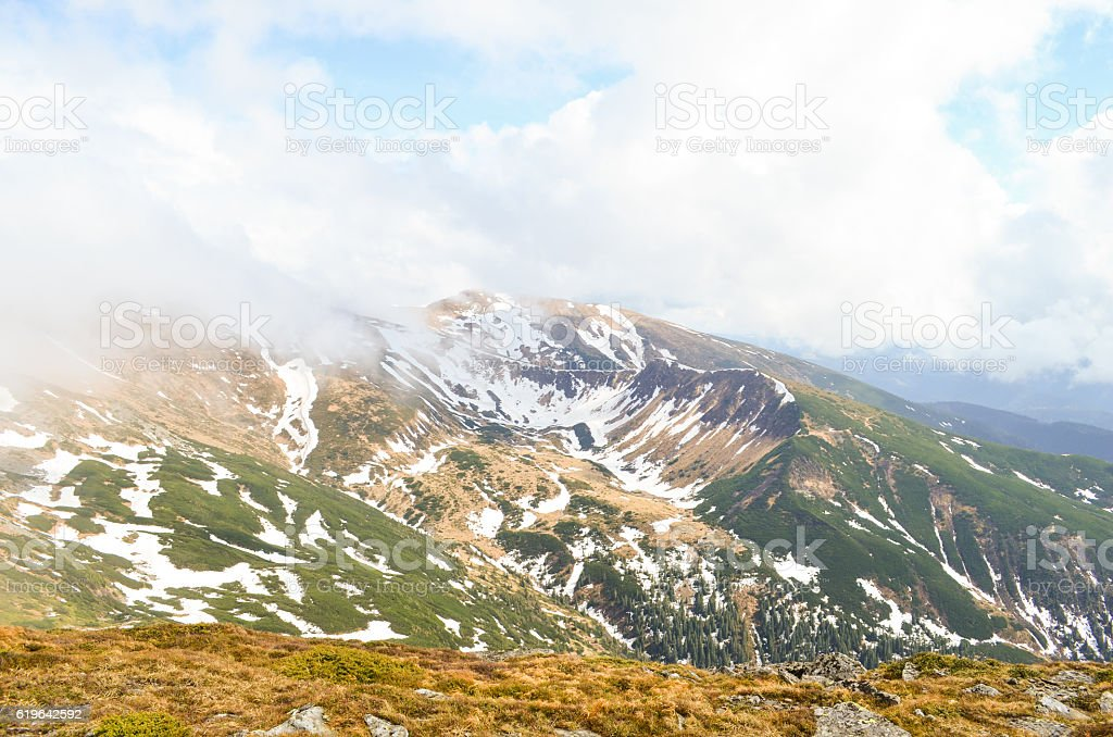 Clouds from a height of snowy mountain stock photo