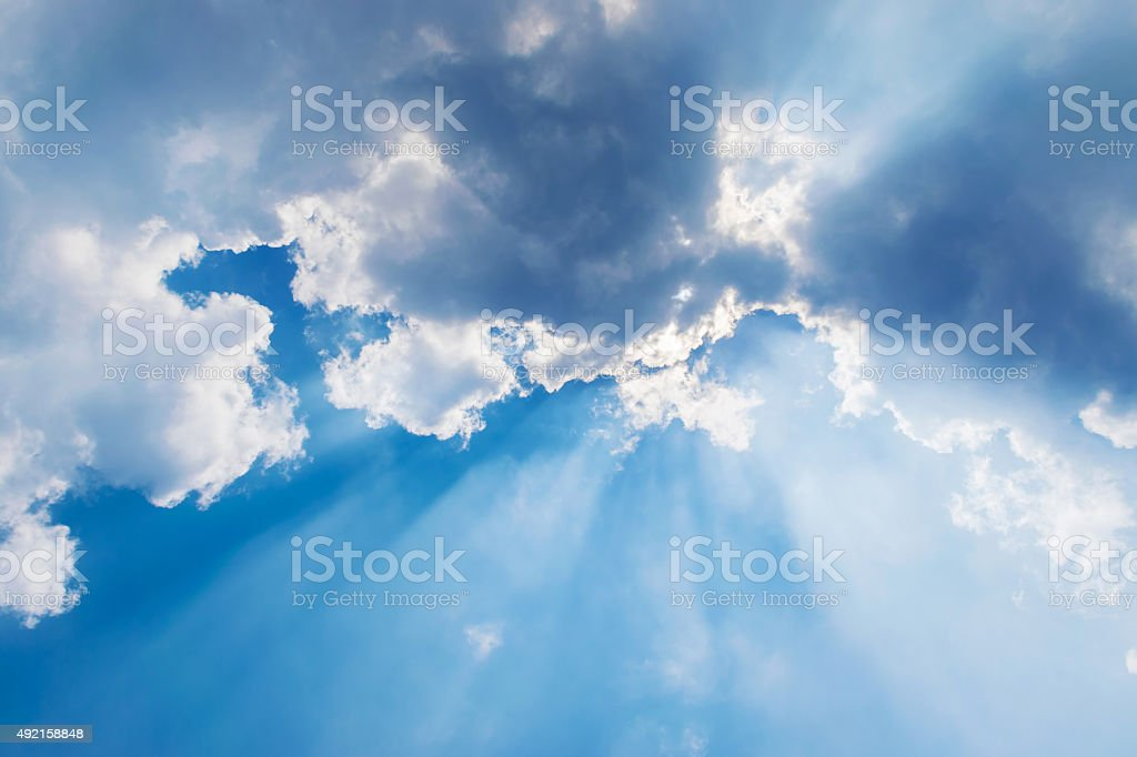 clouds in blue sky with sun rays stock photo