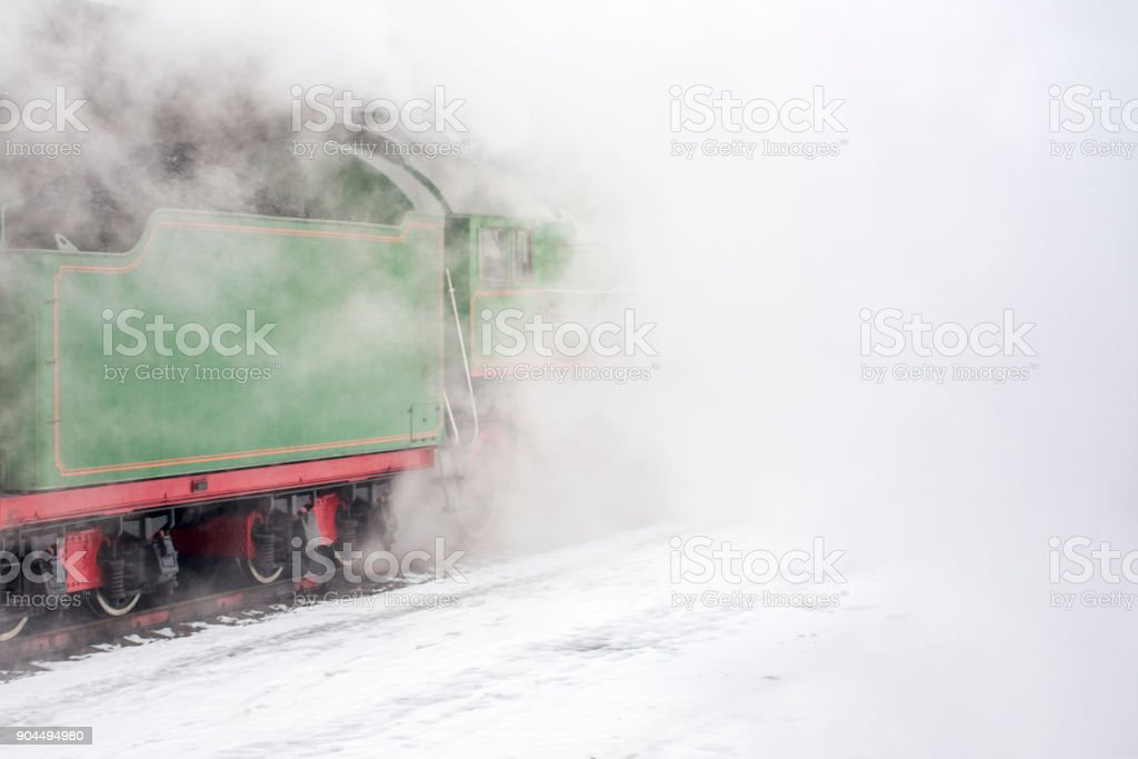 Clouds of vapor around the green steam train. stock photo