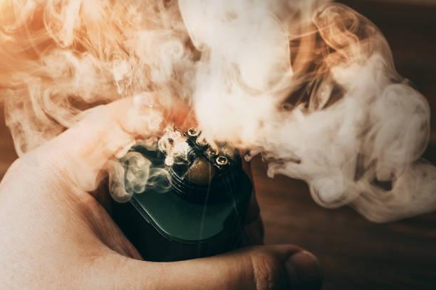 Nuvens de vapor da RDA para vaping na mão de homem, eletrônico moderno vape ou dispositivo ecig - foto de acervo
