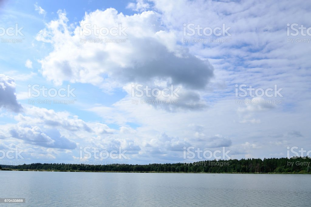 Clouds on blue sky over lake in summer stock photo