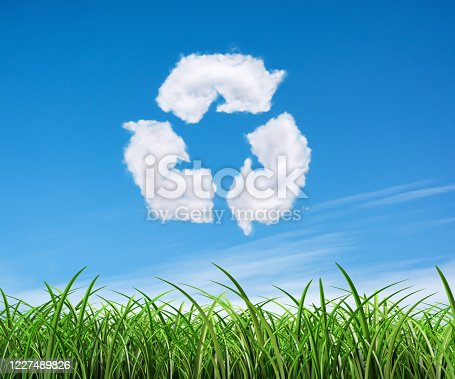 499093370 istock photo Clouds on the blue sky in shape of the symbol of recycling on green background. Protection nature and future concept. 1227489826