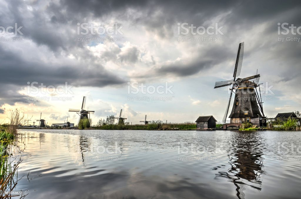 Clouds over a canal in Kinderdijk stock photo