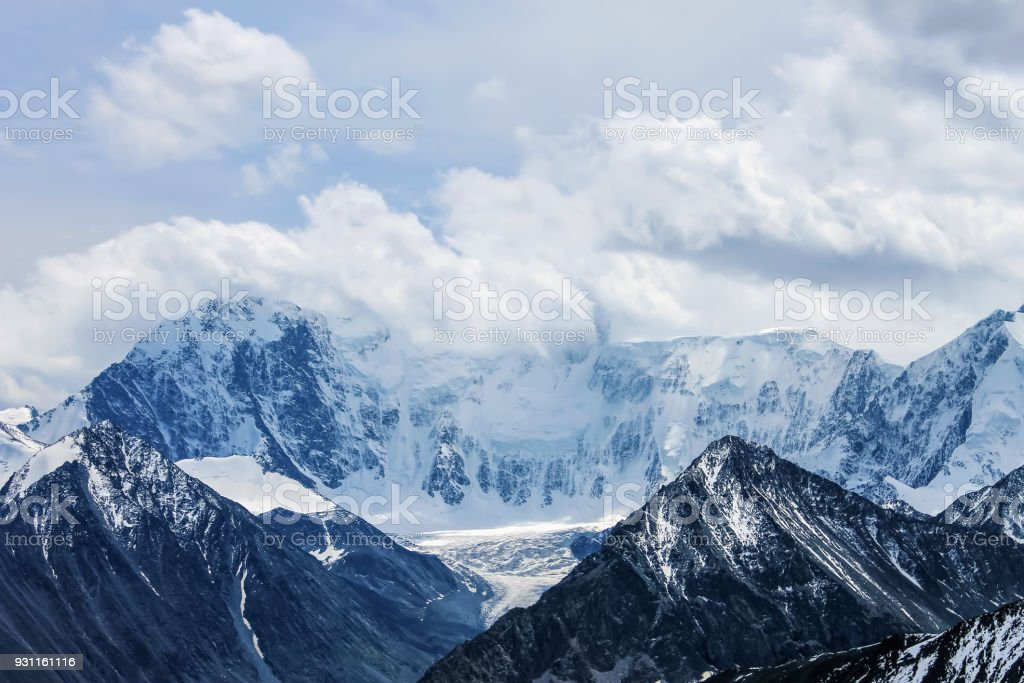Clouds over a mountain covered with snow Belukha from a pass stock photo