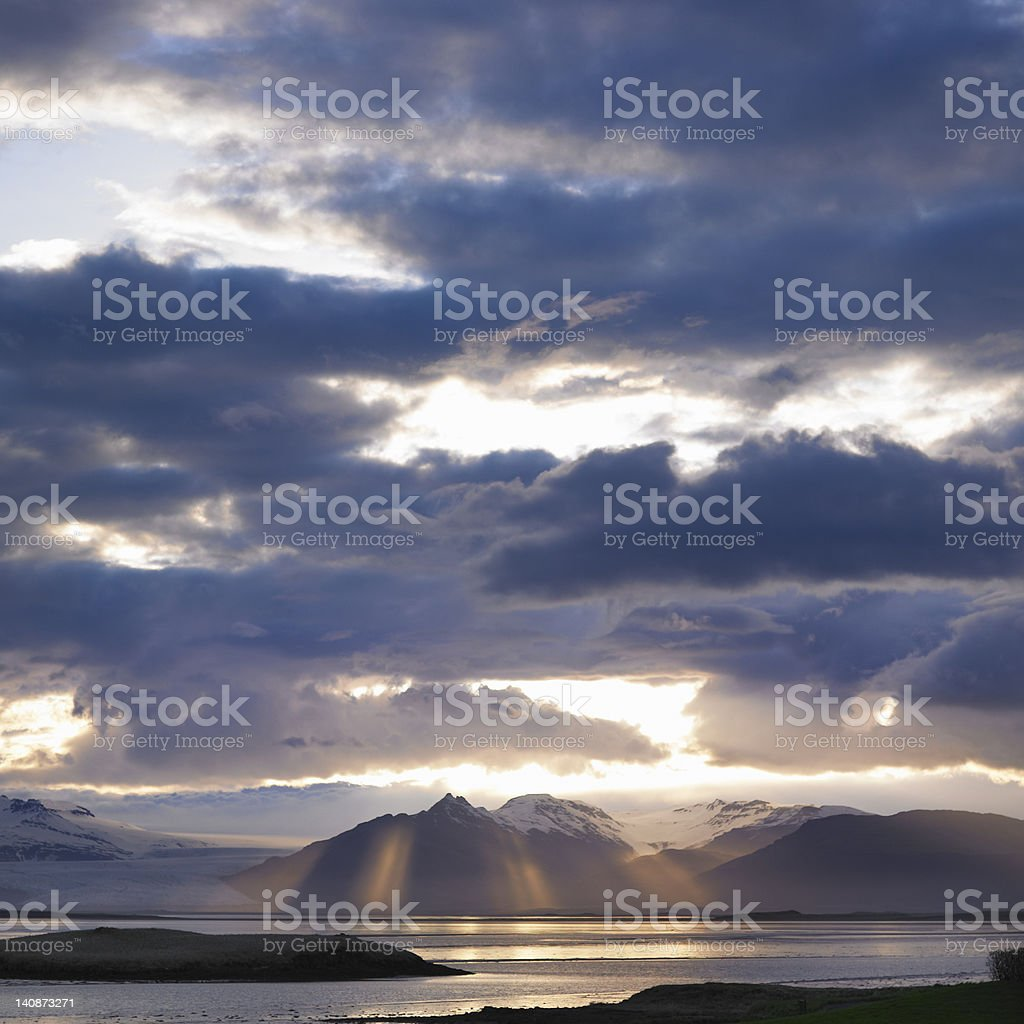 Clouds over mountains and lake stock photo