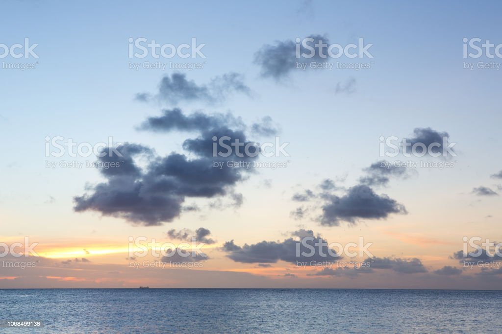 Clouds over ocean and pastel tropical sunset stock photo