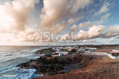 Clouds and flowing sea water over small village on seashore