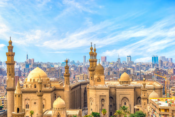 Clouds over Sultan Hassan Mosque Clouds over majestic ancient Sultan Hassan Mosque in Cairo, Egypt minaret stock pictures, royalty-free photos & images