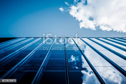 istock Clouds reflected in windows of modern office building 622925970