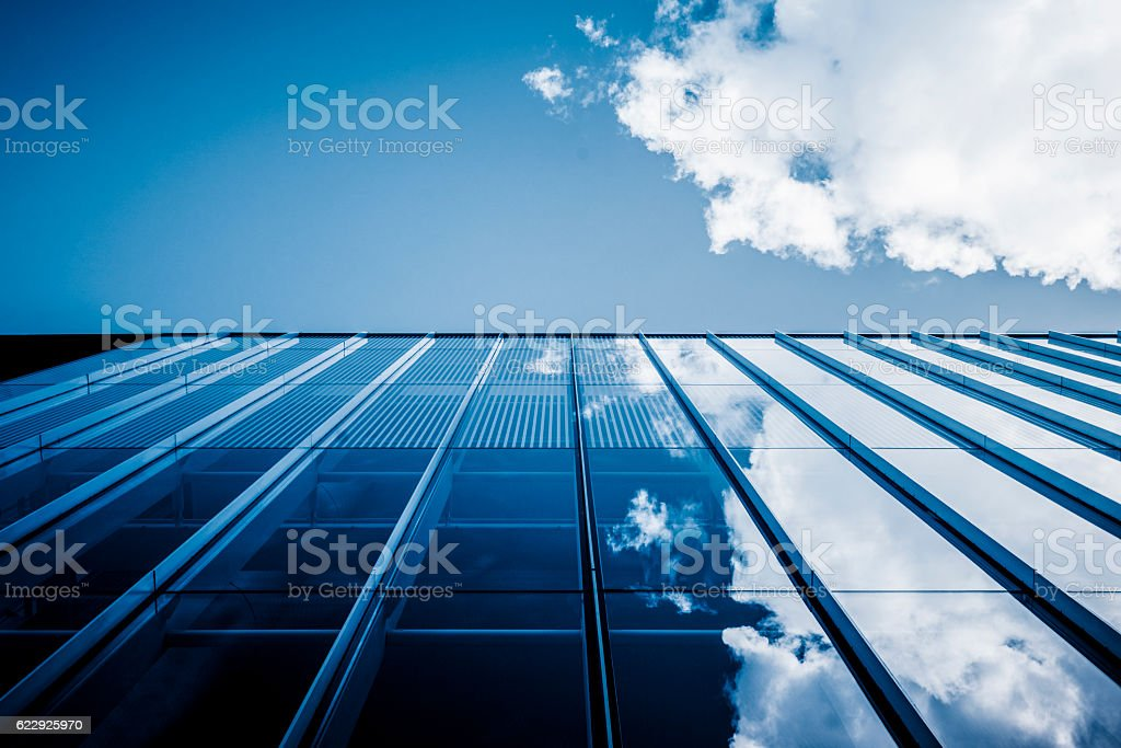 Clouds reflected in windows of modern office building​​​ foto