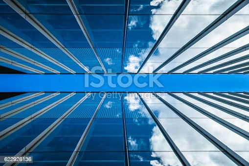 istock Clouds reflected in windows of modern office building 622926136