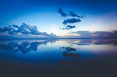 beautiful cloud reflection at seminyak beach on bali island in indonesia.