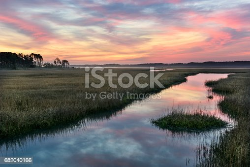 Dawn with clouds reflecting in ocean inlet on Chincoteague Island, Virginia
