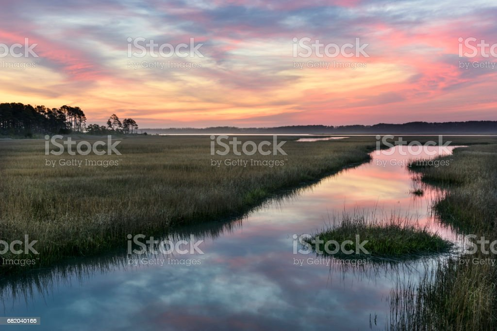 Clouds Reflecting in Water of Salt Marsh at Sunrise stock photo