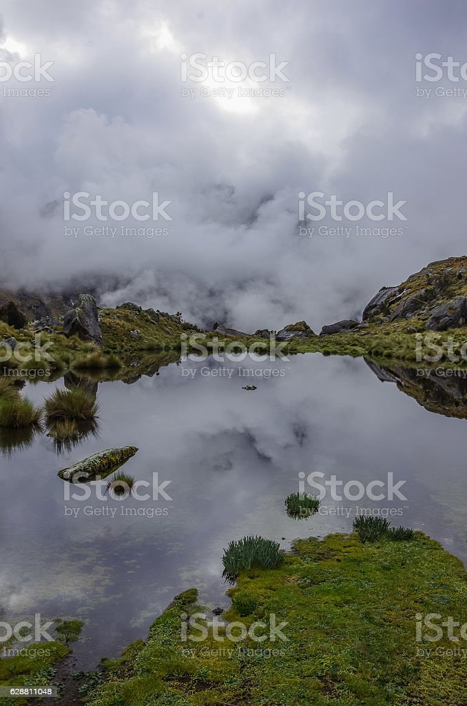 Clouds reflection in mountain lake near Punta Union pass. stock photo