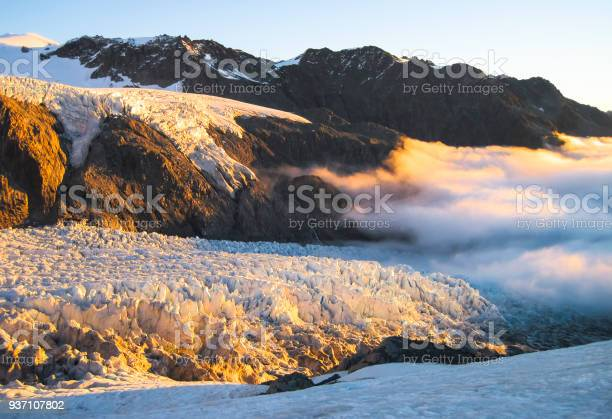 Photo of Clouds Roll in Over the Fox Glacier at Sunset in New Zealand